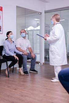 Bezorgd jong stel met gezichtsmasker tegen wachtend nieuws van de dokter