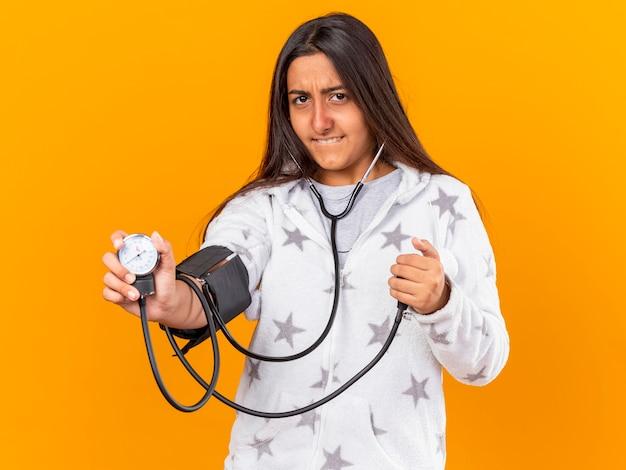 Bezorgd jong ziek meisje dat haar eigen druk meet met bloeddrukmeter die op gele achtergrond wordt geïsoleerd