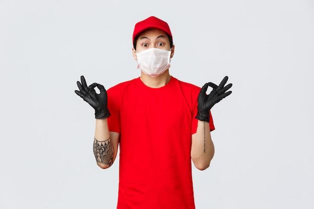 Bezorgd jonge aziatische bezorger proberen kalmeren nerveuze klant, zen gebaar tonen, medische masker en beschermende handschoenen, uniform bedrijf dragen. de koerier maakt een goed teken en zorgt voor de beste kwaliteit