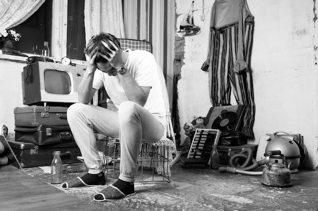 Bezorgd jonge man zittend op de kooi in de rommelkamer in zwart-wit stijl.