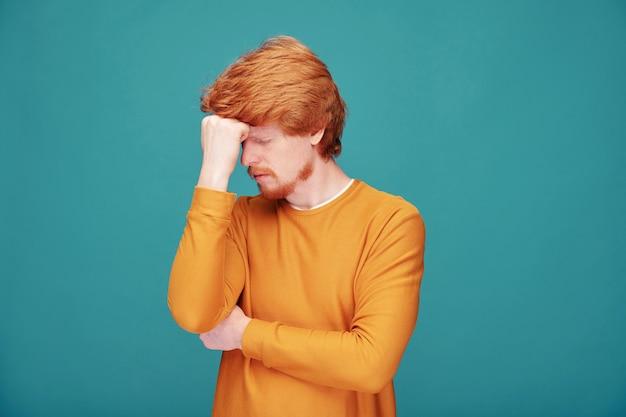 Bezorgd jonge roodharige man met baard gericht op geest wrijven voorhoofd met vuist op blauw