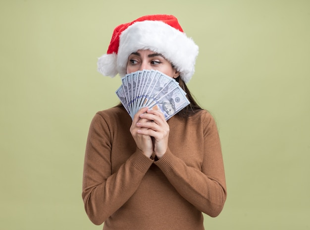 Bezorgd kijken naar kant jong mooi meisje met kerstmuts bedekt gezicht met contant geld geïsoleerd op olijfgroene muur