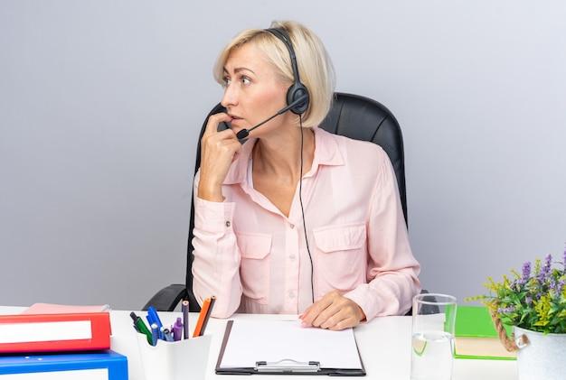 Bezorgd kijkende jonge vrouwelijke callcentermedewerker die een headset draagt die aan tafel zit met kantoorhulpmiddelen geïsoleerd op een witte muur