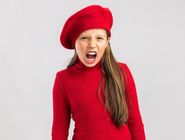 Bezorgd klein blond meisje met een rode baret die naar voren kijkt en schreeuwt geïsoleerd op een witte muur met kopieerruimte