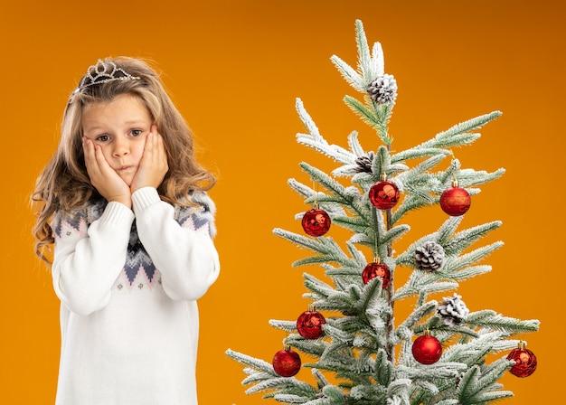 Bezorgd klein meisje dat zich dichtbij kerstboom bevindt die tiara met slinger op hals draagt die handen op wangen legt die op oranje achtergrond worden geïsoleerd