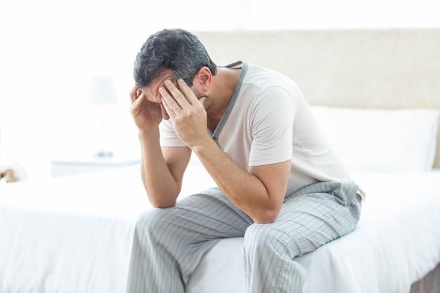 Bezorgd man zittend op bed met de hand op het voorhoofd
