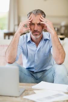 Bezorgd man zittend op de bank met rekeningen en laptop in de woonkamer