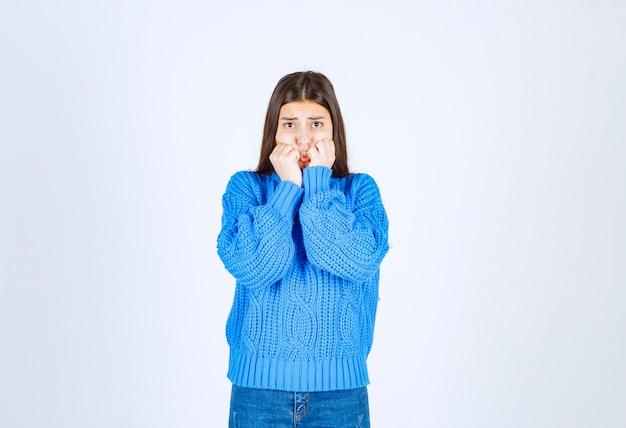 Bezorgd meisjesmodel in warme trui die haar vingers bijt en vooruitkijkt.