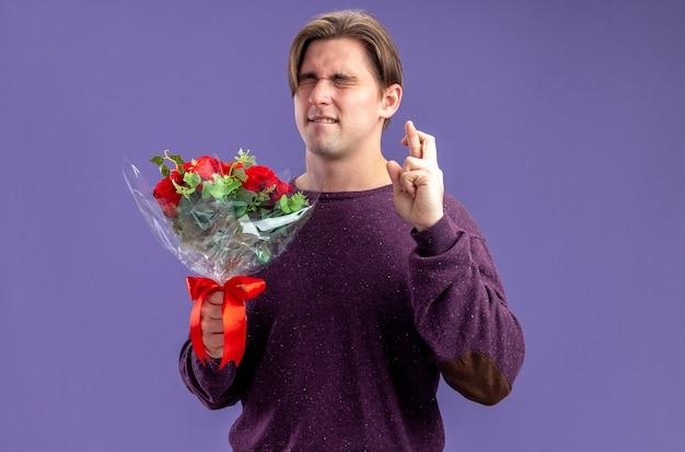 Bezorgd met gesloten ogen jonge kerel op valentijnsdag met boeket kruisende vingers geïsoleerd op blauwe achtergrond