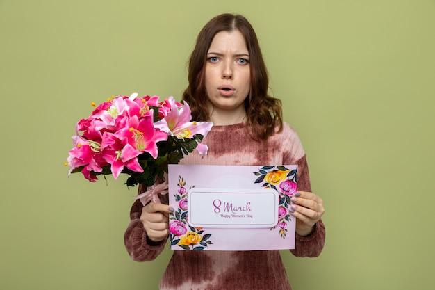 Bezorgd mooi jong meisje op gelukkige vrouwendag met boeket met wenskaart