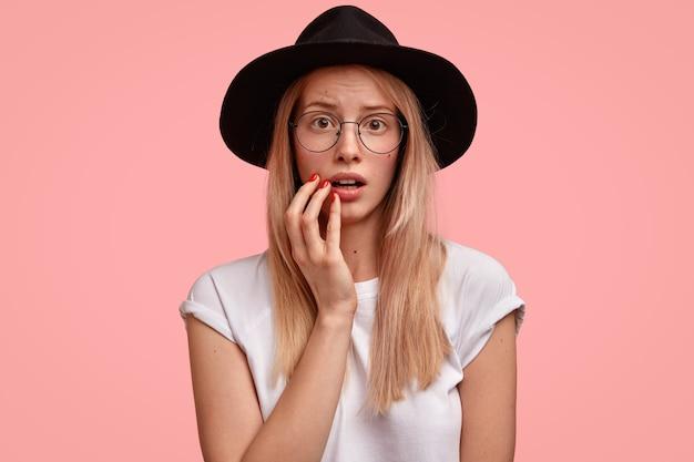 Bezorgd mooie jonge vrouw houdt hand in de buurt van mond, kijkt met beschaamde uitdrukking, hoed en t-shirt