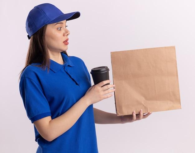 Bezorgd mooie levering vrouw in uniform houdt papier beker en kijkt naar papier pakket op wit