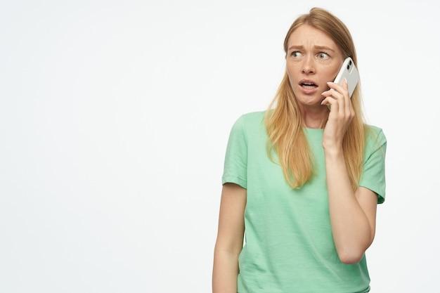 Bezorgd mooie vrouw met sproeten in mint tshirt kijkt bang en praten over mobiele telefoon op wit