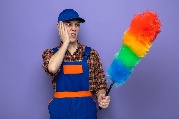 Bezorgd om de hand op de wang te leggen, jonge schoonmaakster met uniform en pet met pipidastre