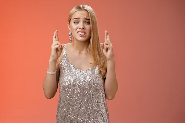 Bezorgd onzeker onzeker hoopvol schattige blonde jonge 25s vrouw zenuwachtig smekend god win kruis vingers veel geluk lip bijten blik intens fronsen in afwachting van resultaten fortuin, biddend rode achtergrond.