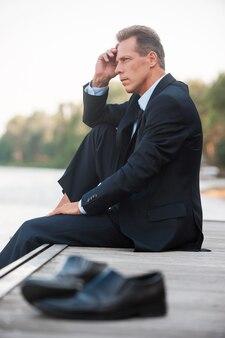 Bezorgd over zijn bedrijf. zijaanzicht van een doordachte zakenman die de hand op de kin houdt en wegkijkt terwijl hij op blote voeten aan de kade zit en met schoenen op de voorgrond