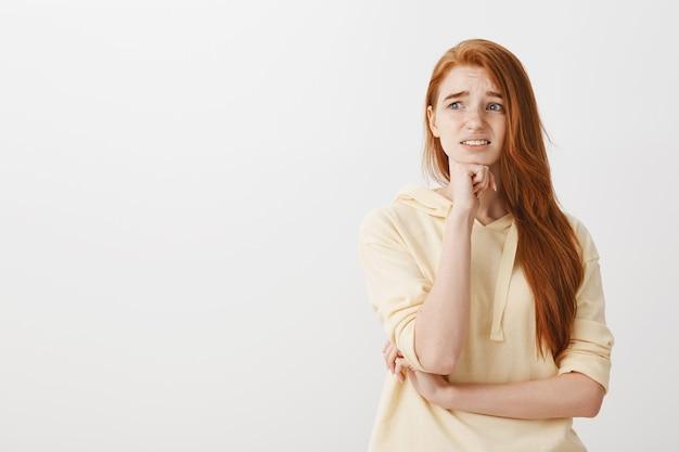 Bezorgd roodharig meisje dat in paniek raakt en er overweldigd uitziet
