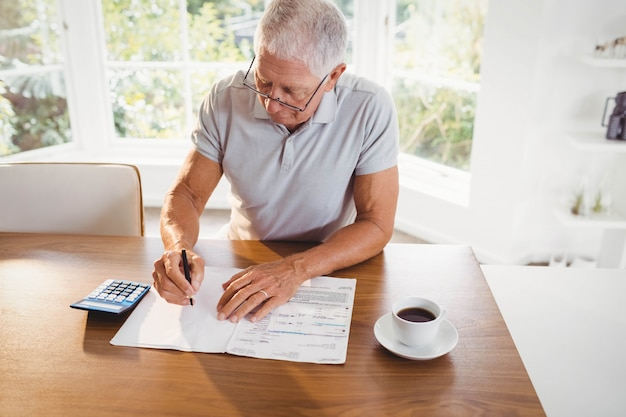 Bezorgd senior man met belastingdocumenten thuis
