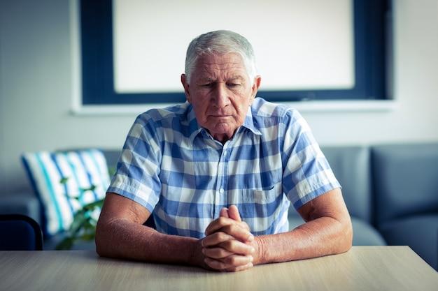 Bezorgd senior man zit in de woonkamer