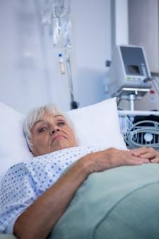 Bezorgd senior patiënt liggend op bed
