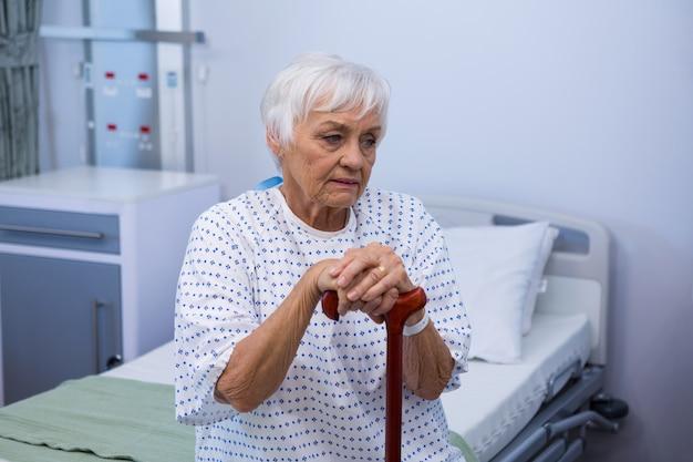 Bezorgd senior patiënt zittend op bed met wandelstok