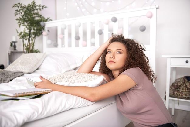 Bezorgd tienermeisje dat aan iets in de slaapkamer denkt