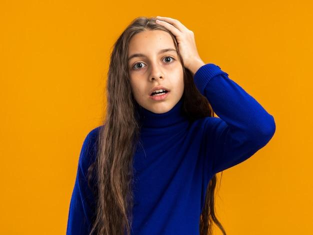 Bezorgd tienermeisje dat naar de voorkant kijkt en de hand op het hoofd houdt geïsoleerd op een oranje muur