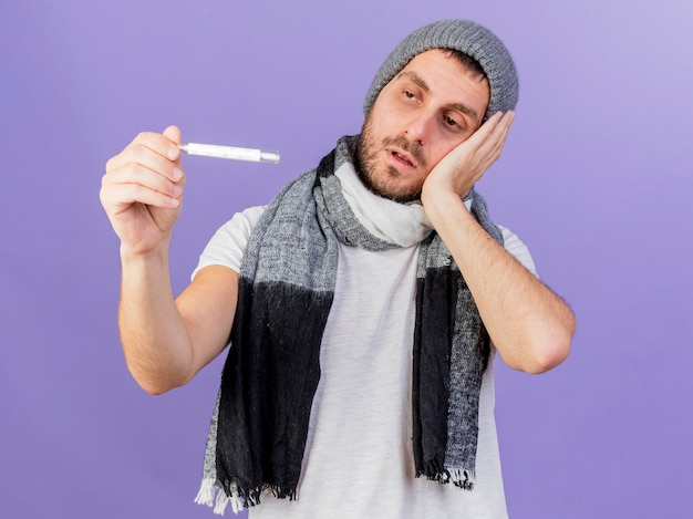 Bezorgd titing hoofd jonge zieke man dragen winter hoed met sjaal houden en kijken naar thermometer hand op wang zetten geïsoleerd op paarse achtergrond