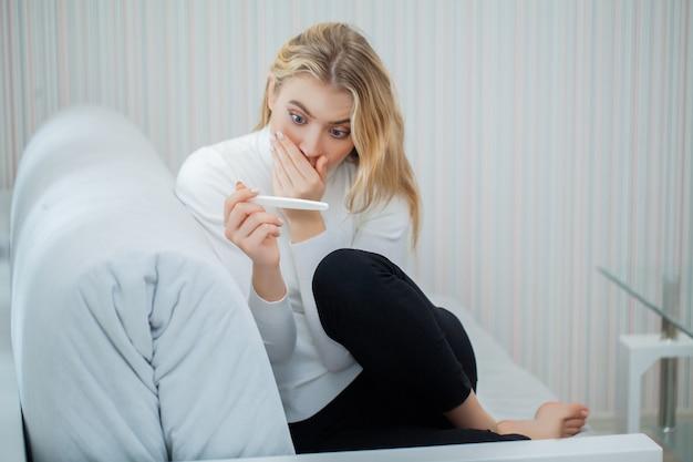 Bezorgd triest vrouw kijken naar een zwangerschapstest na resultaat.