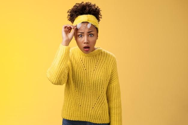 Bezorgd verbaasd sprakeloos afro-amerikaanse student meisje drop kaak opstijgen bril verwijden de ogen verbaasd zijn drop-out kijken ongelooflijk ding, staande ondervraagd gefrustreerd, gele achtergrond.