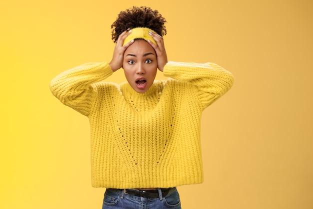 Bezorgd verontrust verrast afro-amerikaanse vrouw hijgend geschokt houd hoofd wijd open ogen verbijsterd gezicht lastige situatie paniek onbewust wat doen, staande gefrustreerde gele achtergrond.