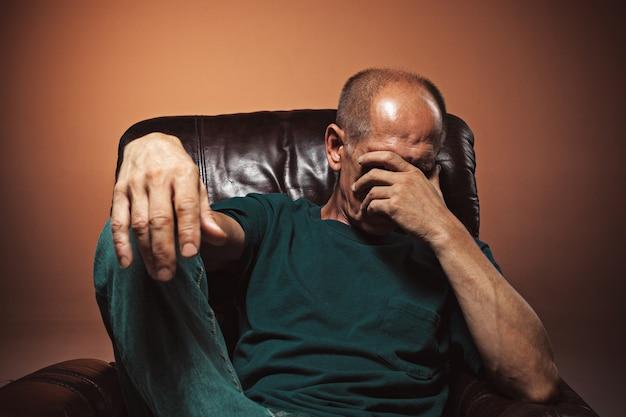 Bezorgd volwassen man zijn hoofd aan te raken.