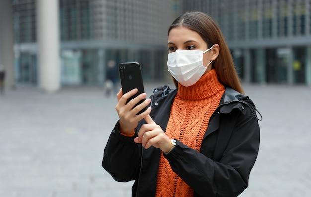 Bezorgd vrouw met beschermend masker lezen van informatie op haar smartphone in moderne stad straat