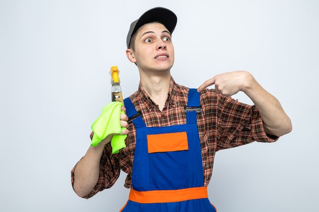 Bezorgd wijst naar zichzelf, jonge schoonmaakster in uniform en pet met vod met schoonmaakmiddel