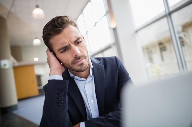 Bezorgd zakenman zit aan bureau met laptop
