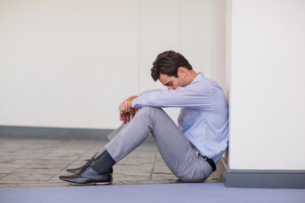 Bezorgd zakenman zittend op de vloer