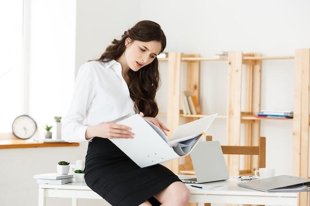 Bezorgd zakenvrouw lezen van een meldingsrapport terwijl zittend in een bureau op kantoor werkt.