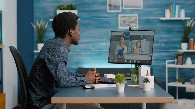 Bezorgde afro-amerikaanse vader voor haar kleine meisje in de ziekenhuisafdeling die aan het praten is tijdens een videoconferentiegesprek