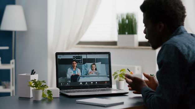 Bezorgde afro-amerikaanse vader voor klein meisje in ziekenhuisafdeling, pratend met arts op videoconferentiegesprek met webcam-app op afstand scherm voor familieverbinding. huisarts consult via internet