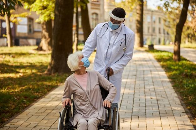 Bezorgde arts die een plastic gelaatsscherm draagt, vraagt zijn patiënt in een rolstoel of ze zich goed voelt