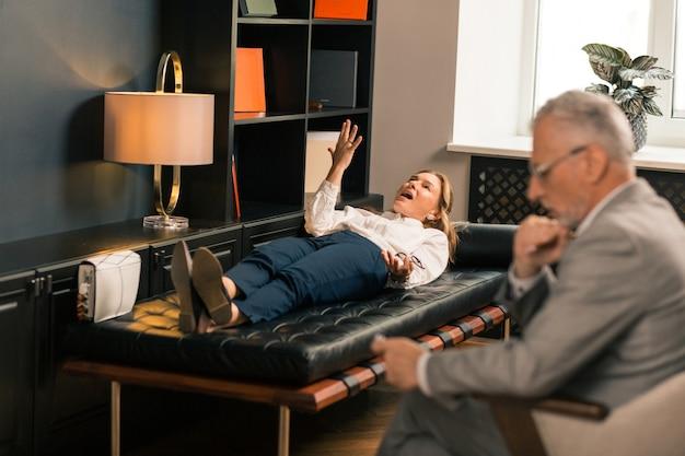 Bezorgde blanke vrouw van middelbare leeftijd liggend op de bank in het kantoor van haar psychotherapeut terwijl ze met hem praat
