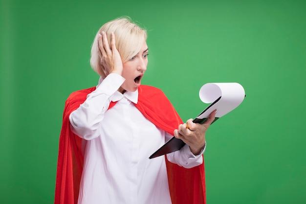 Bezorgde blonde superheldenvrouw van middelbare leeftijd in rode cape die klembord vasthoudt en hand op het hoofd zet