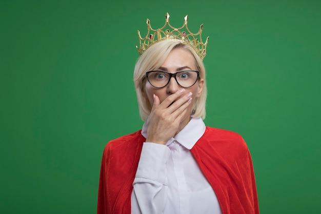 Bezorgde blonde superheldenvrouw van middelbare leeftijd in rode cape met een bril en een kroon die de hand op de mond houdt