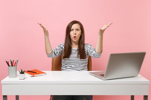 Bezorgde boze vrouw in verbijstering vloekend spreidende handen zitten en werken aan een wit bureau met hedendaagse pc-laptop geïsoleerd op pastelroze achtergrond. prestatie zakelijke carrière concept. ruimte kopiëren.
