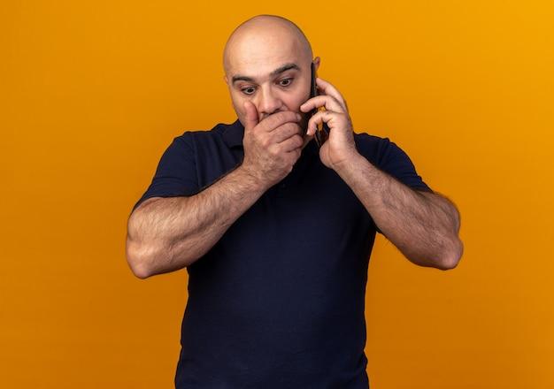 Bezorgde casual man van middelbare leeftijd die aan de telefoon praat terwijl hij zijn hand op de mond houdt en naar beneden kijkt, geïsoleerd op een oranje muur