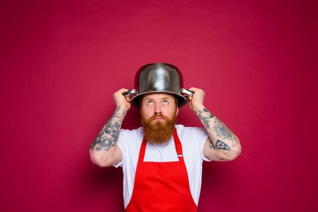 Bezorgde chef-kok met baard en rode schort speelt met pot