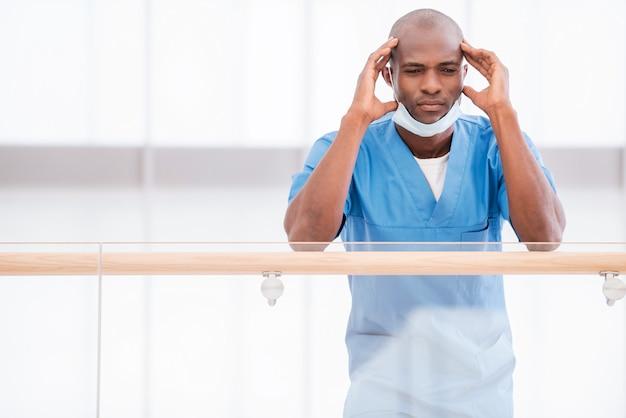 Bezorgde chirurg. lage hoek van depressieve jonge afrikaanse arts in blauw uniform die zijn hoofd met handen aanraakt en wegkijkt terwijl hij naar de leuning leunt