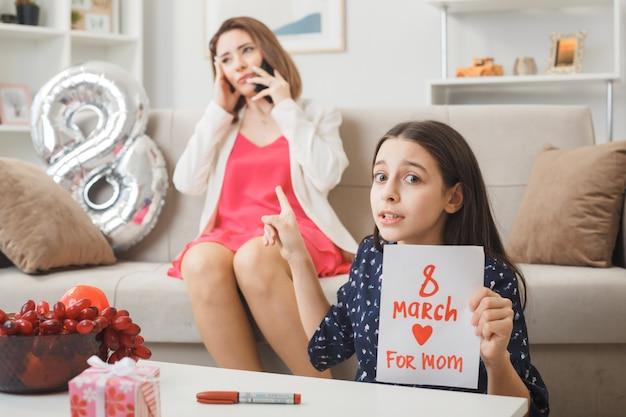 Bezorgde dochter met wenskaart zittend op de vloer achter salontafel op gelukkige vrouwendag moeder zittend op de bank spreekt aan de telefoon in de woonkamer
