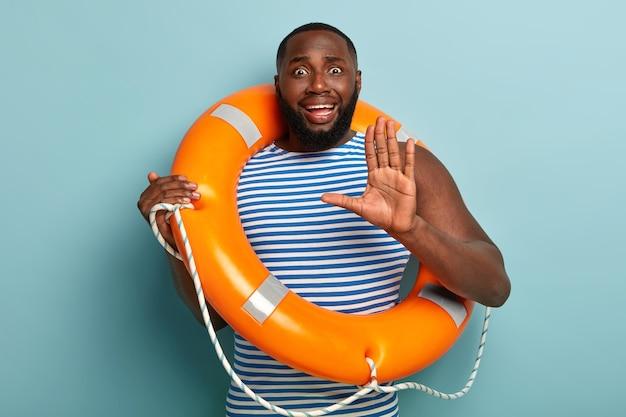 Bezorgde donkere man weigert te zwemmen, maakt stopgebaar met handpalm, draagt lifering
