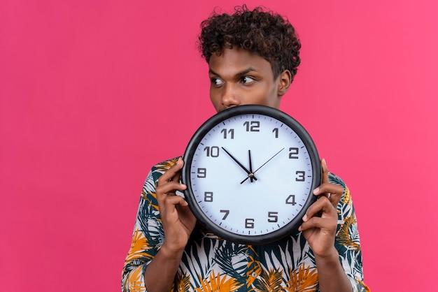 Bezorgde en bedachtzame jonge donkere man met krullend haar in bladeren bedrukt overhemd met wandklok met tijd terwijl hij naar de zijkant op een roze achtergrond kijkt